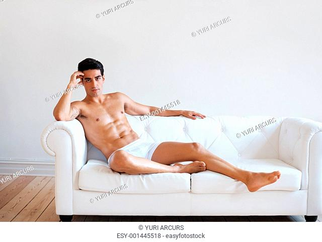 Portrait of a muscular young guy in underwear posing on couch at home