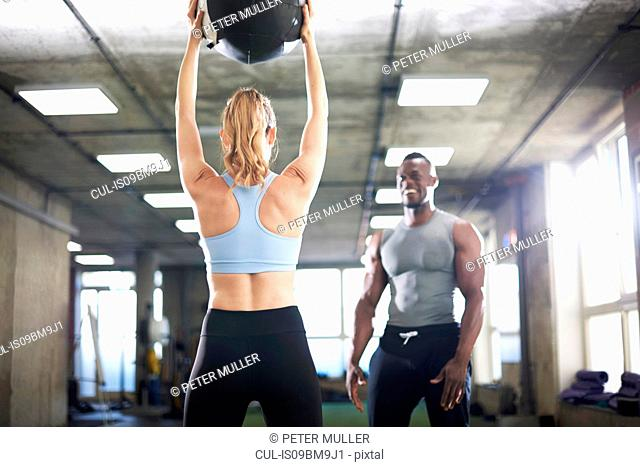Trainer watching female client lift medicine ball in gym
