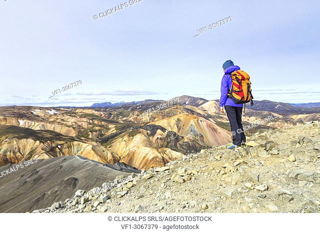 A trekker is looking at the Landmannalaugar panorama from the top of Blahnukur mountain (Landmannalaugar, Fjallabak Nature Reserve, Highlands, Southern Region