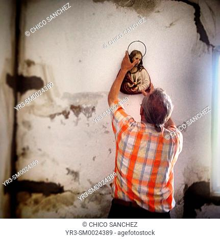 A man holds an image of Jesus Christ in his home in Prado del Rey, Sierra de Grazalema, Andalusia, Spain