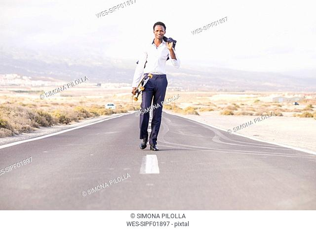 Spain, Tenerife, young businessman with skateboard walking on road
