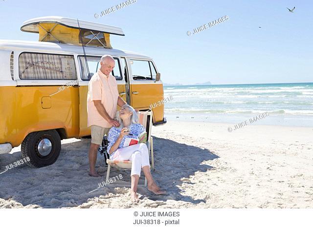 Senior couple relaxing outside van on sunny beach