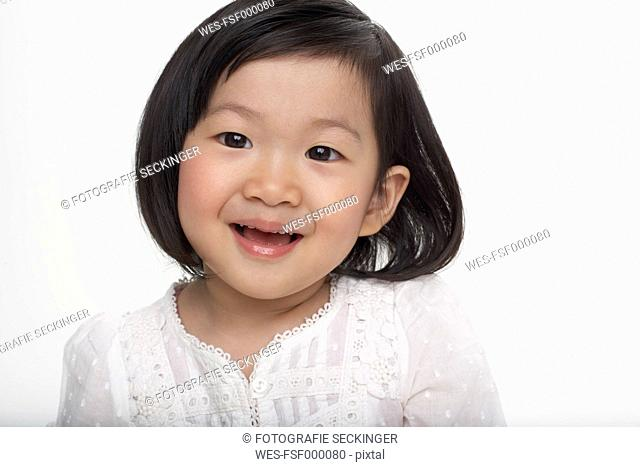 Portrait of little Asian girl smiling, studio shot