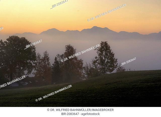 Morning light at Gasthof Weingarten inn with Hochfelln and Hochgern mountains, Greimharting, Rimsting, Ratzinger Hoehe, Upper Bavaria, Germany, Europe