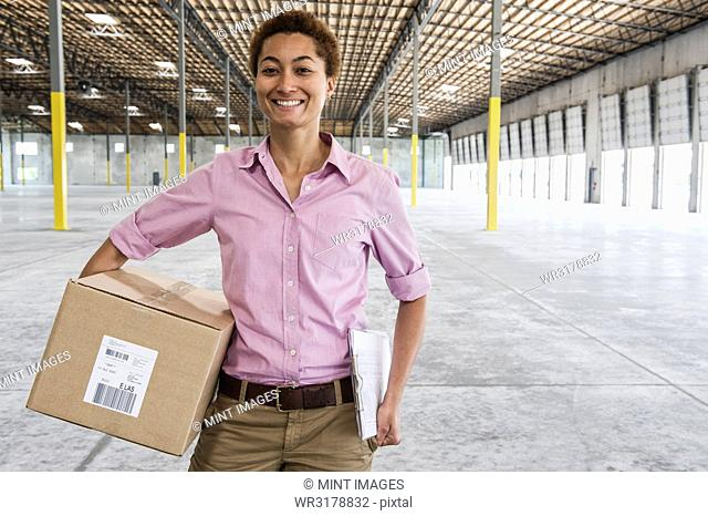Black female holding cardboard box and standing in front of loading dock doors in a new empty warehouse
