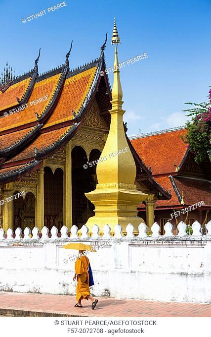 Young novice monks walk past Wat Sop in Luang Prabang, Laos