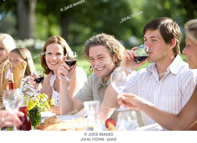 Group of guests drinking wine at an outdoor reception