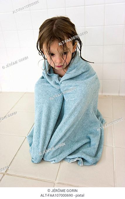 Little girl wrapped in a towel, looking down sadly
