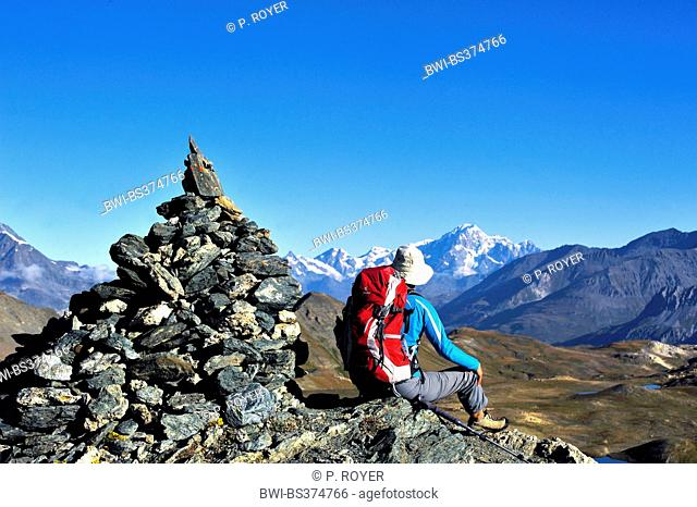 wanderer sitting next to a pile of stones and looking to the Mont Blanc, France, Savoie, Vanoise National Park, Val d Isere Tignes