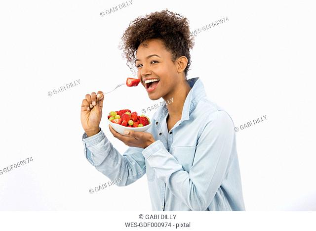 Portrait of happy young woman eating fruits in front of white background
