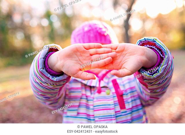Portrait of young caucasian girl holding her in front of her face in a gesture suggesting to leave her alone