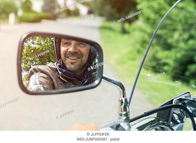 Reflection of smiling man in mirror of motorbike