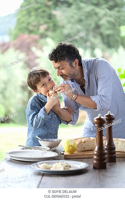 Father and son eating bread