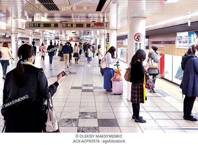People waiting for a train on a Tokyo Metro subway station platform. Tokyo, Japan
