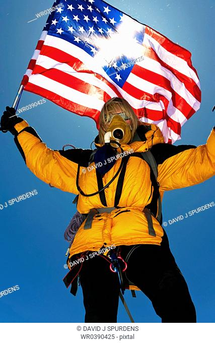 A mountaineer with oxygen breathing apparatus celebrates and waves the US flag after achieving the summit