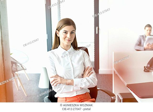 Portrait confident brunette businesswoman with arms crossed in office