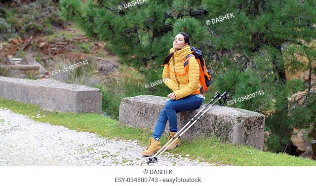 Attractive young woman hiking in the mountains on a gravel trail taking a rest on a retaining wall enjoying the peace and quiet panoramic with copy space