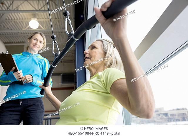 Trainer guiding woman at weight machine