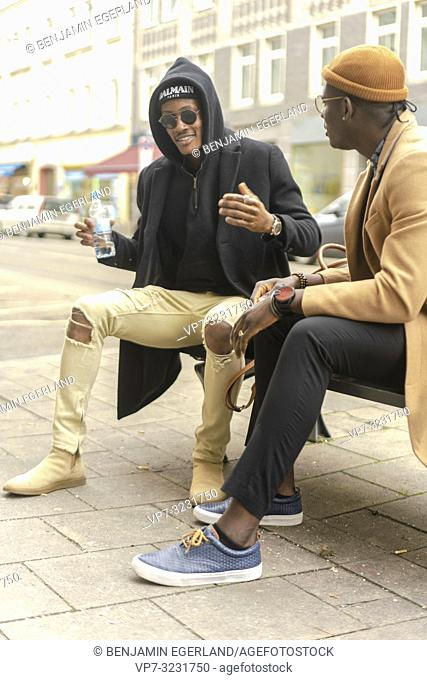 two fashionable male friends sitting together at bench at street in city and talking, conversation, in Munich, Germany