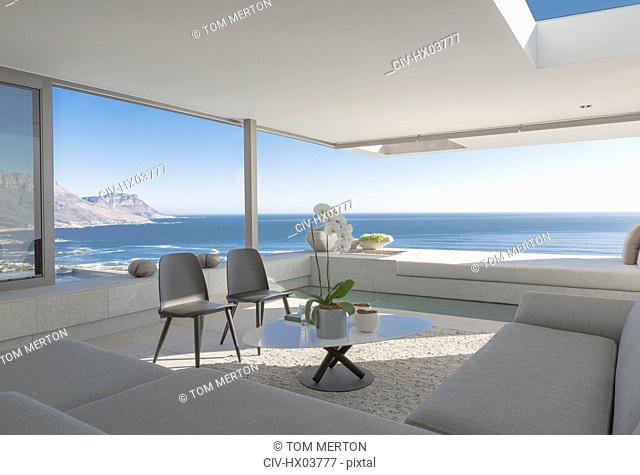 Modern, luxury home showcase interior living room open to sunny ocean view