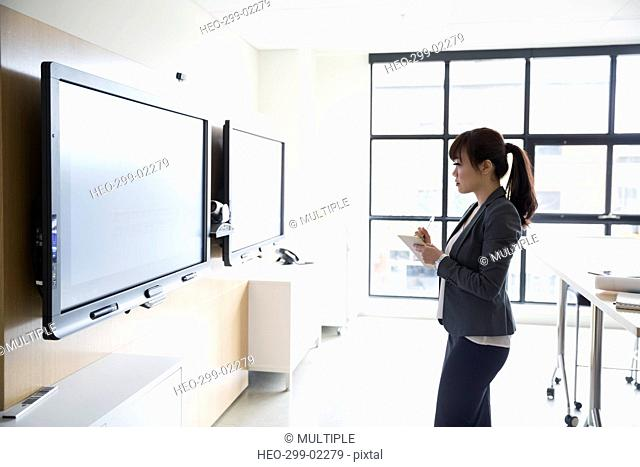 Businesswoman taking notes at television in conference room