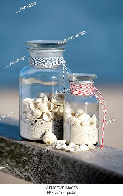 Two pharmacy bottles filled with sand and shells