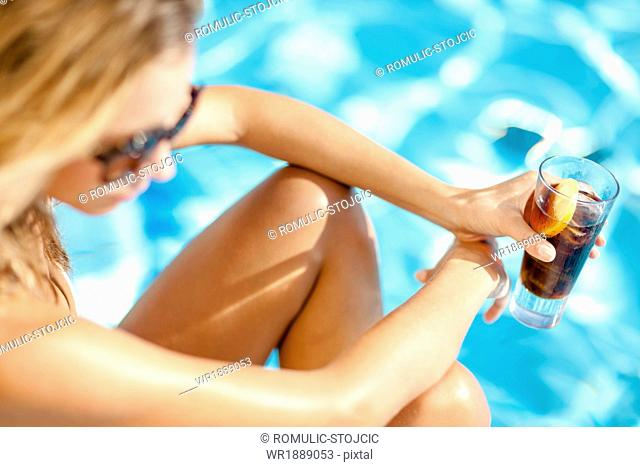 Young woman drinking cocktail on the poolside, Dubrovnik, Croatia