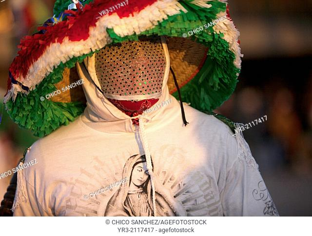 A dancer from Chocaman, Veracruz, wearing a shirt with the image of Our Lady of Guadalupe and wearing a mask, dances the Danza de los Santiagos at the...