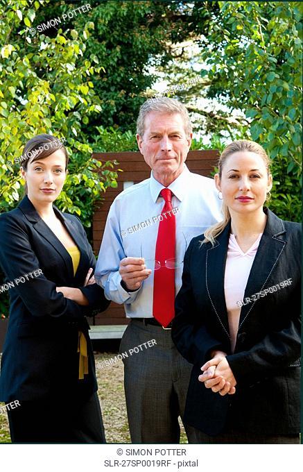 Confident business trio outdoors