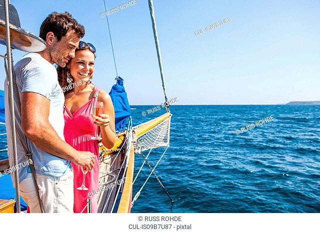 Couple standing on boat, on water, holding champagne flutes, looking at view