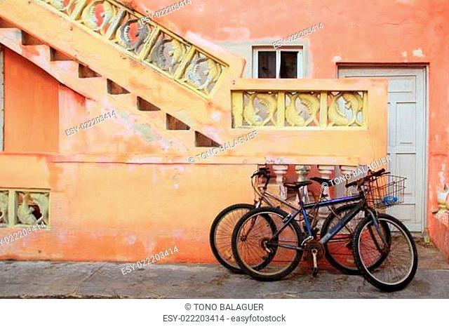 bicycles on grunge tropical Caribbean orange facade