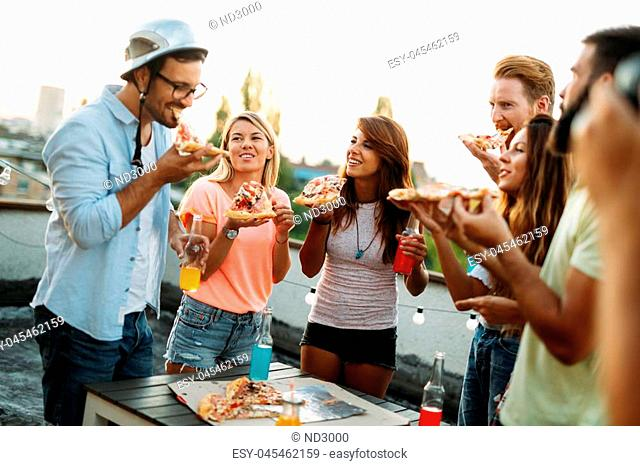 Group of happy young friends having party on rooftop