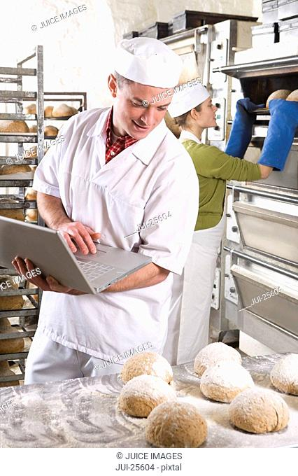 Baker with laptop looking at fresh loaves of bread