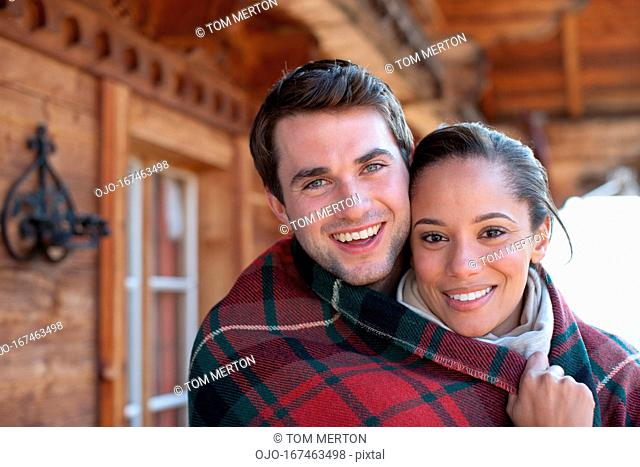 Portrait of smiling couple wrapped in a blanket on cabin porch