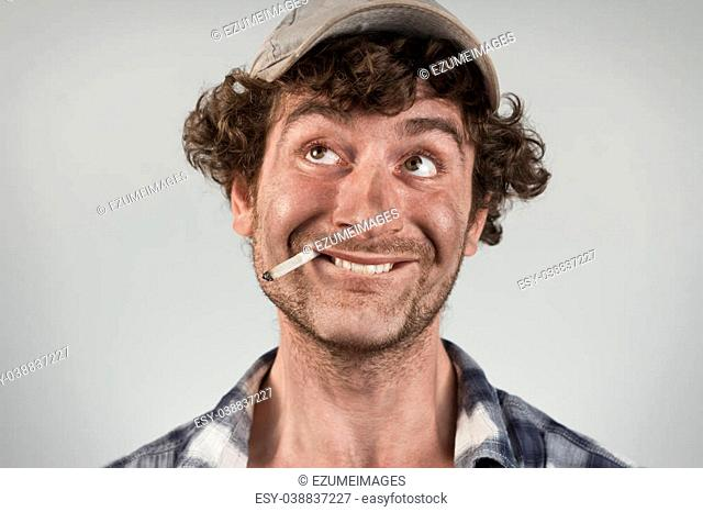 Silly redneck smokes cigarette and bites lip thinking of good fortune