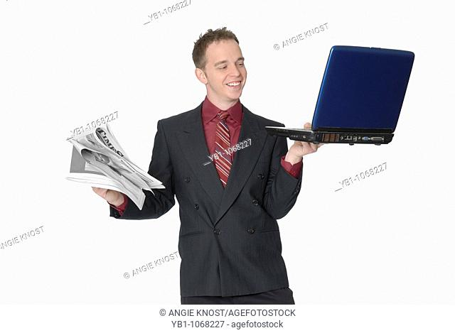 Business man with laptop and newspaper
