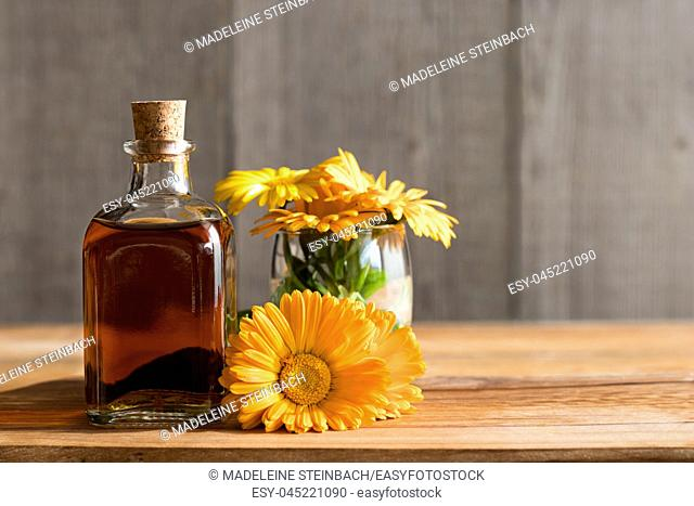 A bottle of calendula (marigold) tincture with fresh calendula flowers on a wooden background