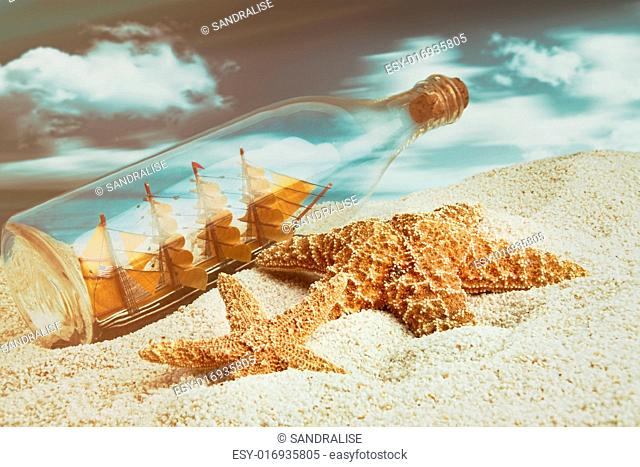 Bottle with ship inside on the beach with starfish
