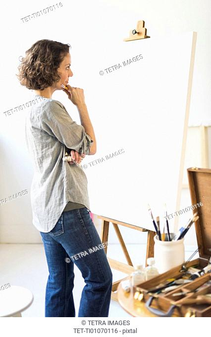 Artist standing in front of canvas
