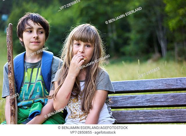 young girl eating snack during rest of hiking adventure with brother