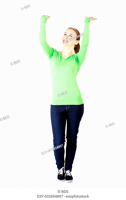 Smiling young woman is holding something abstract above her head. Happy girl with raised hands. Isolated on white background