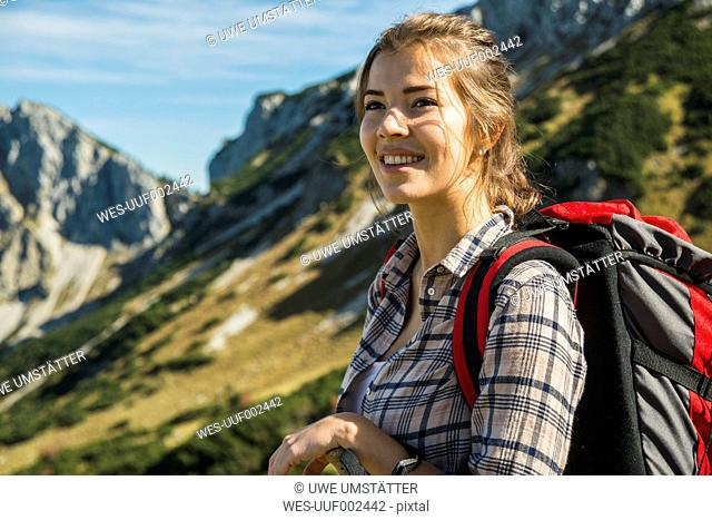 Austria, Tyrol, Tannheimer Tal, smiling young woman on hiking trip
