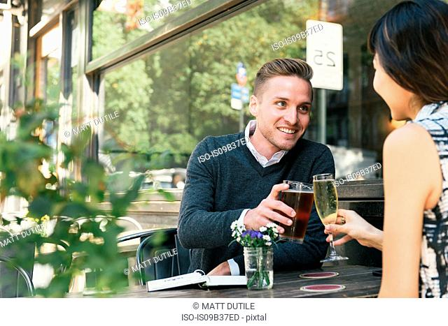 Young couple raising a toast outside restaurant