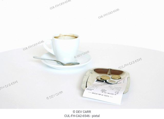 Empty expresso cup and bill with change in a saucer