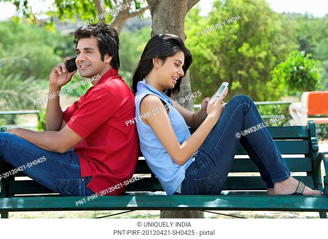 Couple using mobile phones in a park, Japanese Park, Rohini, Delhi, India