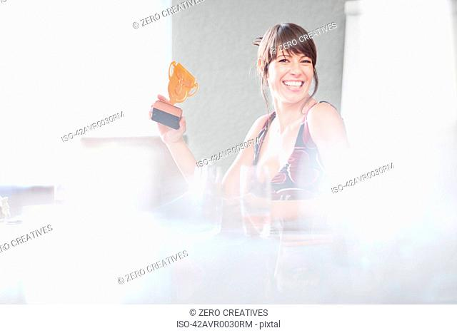 Businesswoman holding trophy