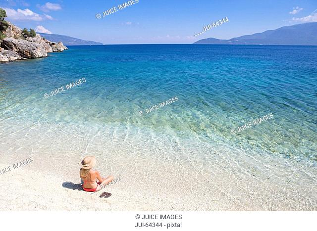 Woman, looking out to sea, sitting on sunny beach