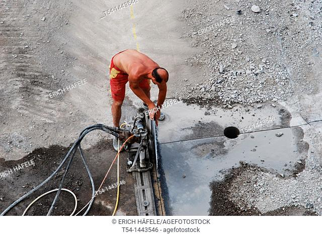 A worker uses disassemble a concrete saw when a highway bridge