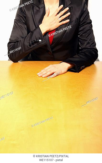 View of a business-woman sitting at the desk gesturing