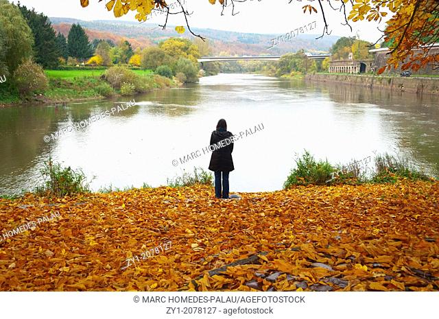 Autumn scene. Pensive woman at the river in Hannover Münden Germany